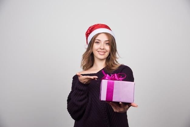 현재 선물 상자를 보여주는 산타 모자에 젊은 여자.