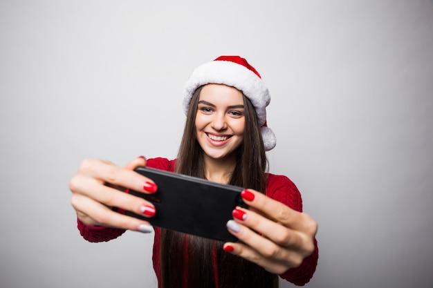 サンタの帽子をかぶった若い女性は灰色の壁に隔離の電話で自分撮りを取ります