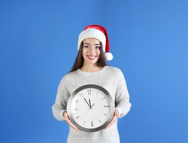 시계와 산타 모자에 젊은 여자. 크리스마스 카운트다운 개념
