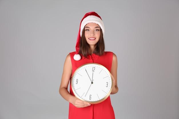 시계와 산타 모자에 젊은 여자. 새해 카운트다운 개념