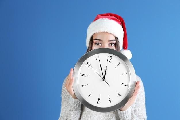 색상 배경에 시계와 산타 모자에 젊은 여자. 크리스마스 카운트다운 개념