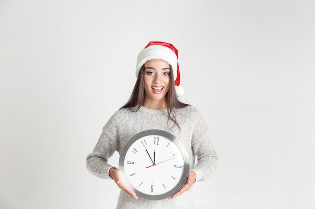 밝은 배경에 시계와 산타 모자에 젊은 여자. 크리스마스 카운트다운 개념