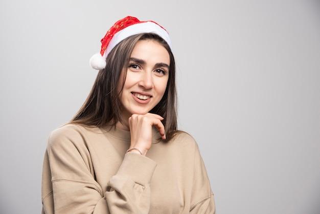 サンタさんの帽子をかぶったスタジオショットの若い女性が灰色で隔離。