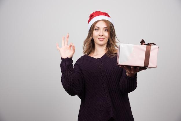Молодая женщина в шляпе санты с подарком, показывающим одобренный жест.