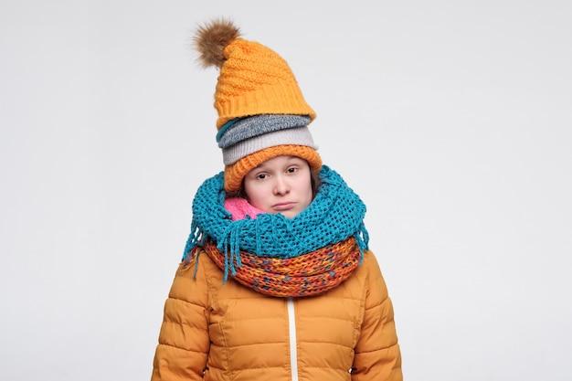 いくつかの帽子とスカーフの若い女性