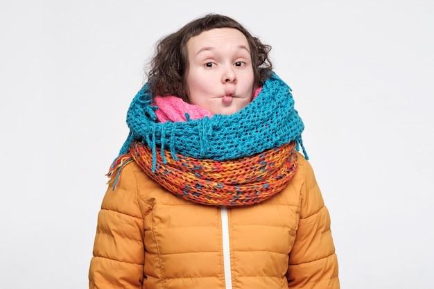 面白いしかめっ面を作るいくつかのスカーフの若い女性