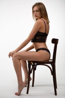 Молодая женщина в сексуальном кружевном нижнем белье, сидя на стуле