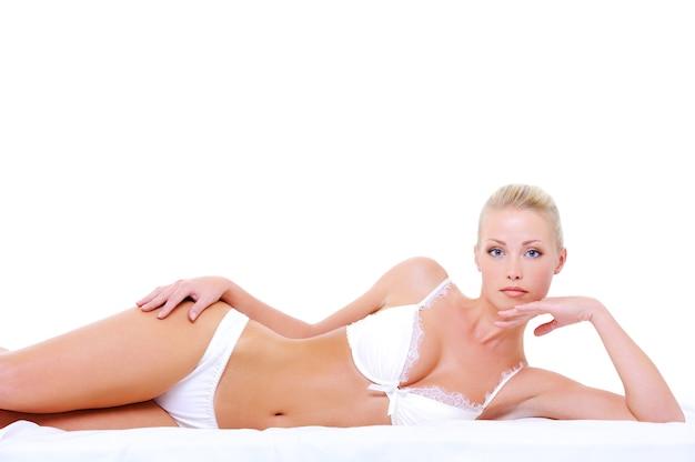 매혹적인 포즈에 누워 섹시한 흰색 란제리에 젊은 여자
