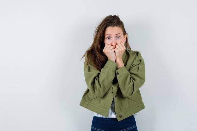 シャツを着た若い女性、感情的に拳を噛み、おびえているように見えるジャケット、正面図。