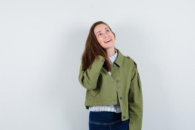 シャツを着た若い女性、首に手を握って幸せそうに見えるジャケット、正面図。
