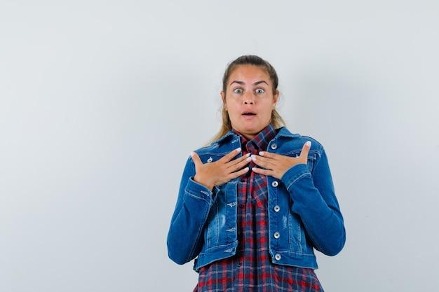 Молодая женщина в рубашке, куртке, взявшись за руки на груди и озадаченно глядя, вид спереди.