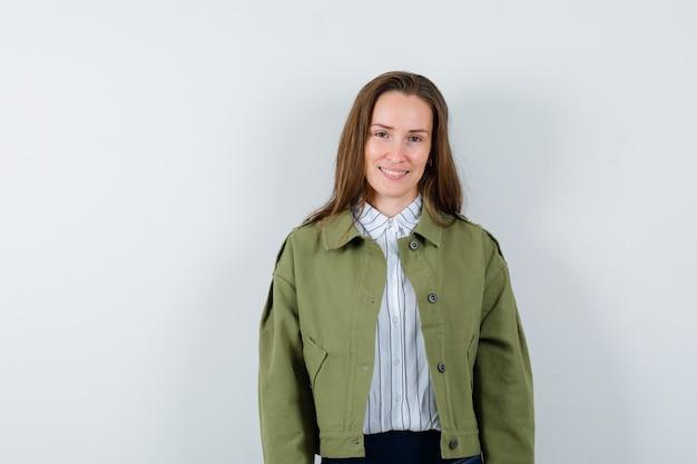 Молодая женщина в рубашке, куртке, глядя на камеру и уверенно глядя, вид спереди.