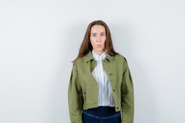 Молодая женщина в рубашке, куртке, глядя на камеру и озадаченно глядя, вид спереди.
