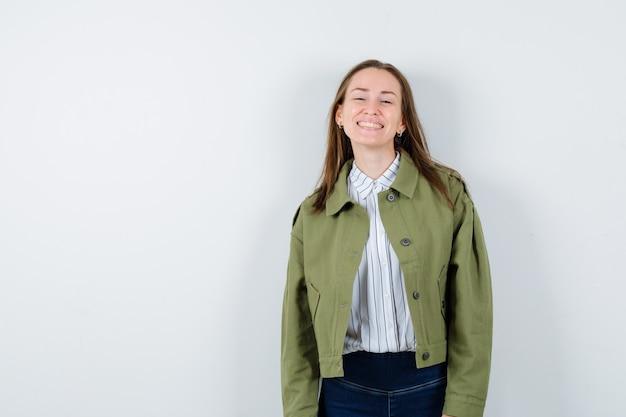 Молодая женщина в рубашке, куртке, глядя на камеру, смеясь и выглядя элегантно, вид спереди.