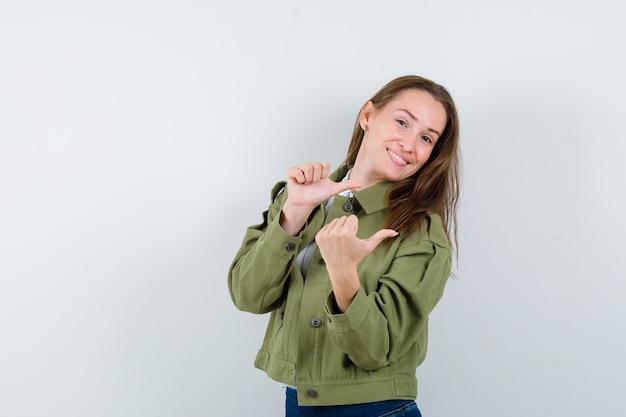 シャツを着た若い女性、親指で脇を向いて陽気に見えるジャケット、正面図。