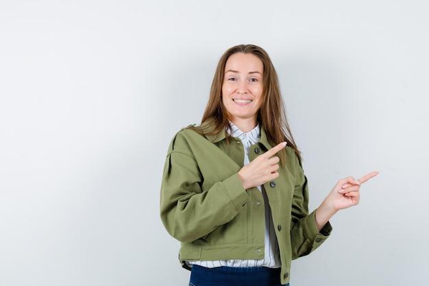 シャツを着た若い女性、右上隅を指し、陽気に見えるジャケット、正面図。