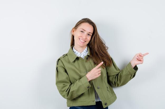 シャツを着た若い女性、右側を指し、陽気に見えるジャケット、正面図。