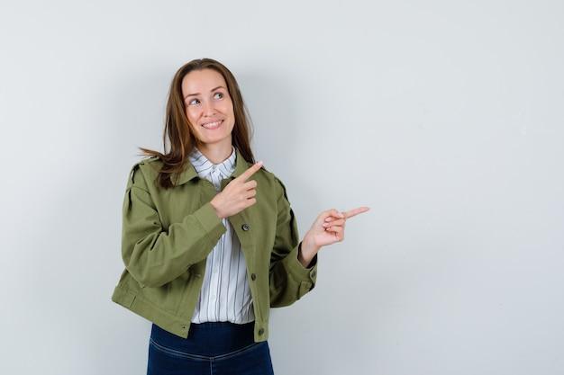 シャツを着た若い女性、右側を指し、夢のような正面図のジャケット。