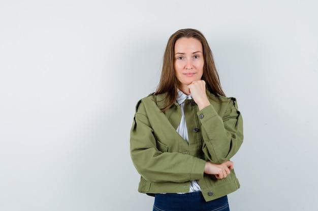 Молодая женщина в рубашке, куртке, подпирая подбородок кулаком и выглядящей разумно, вид спереди.