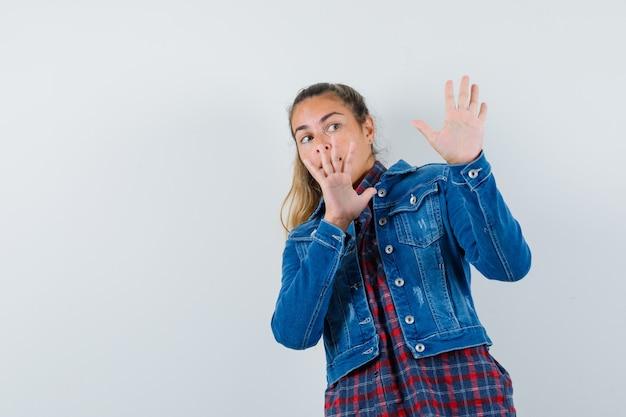 셔츠에 젊은 여자, 재킷 손을 들고 자신을 방어하고 무서워, 전면보기를 찾고.