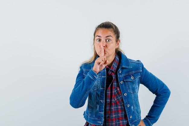 Молодая женщина в рубашке, куртке показывает жест молчания и смотрит осторожно, вид спереди.