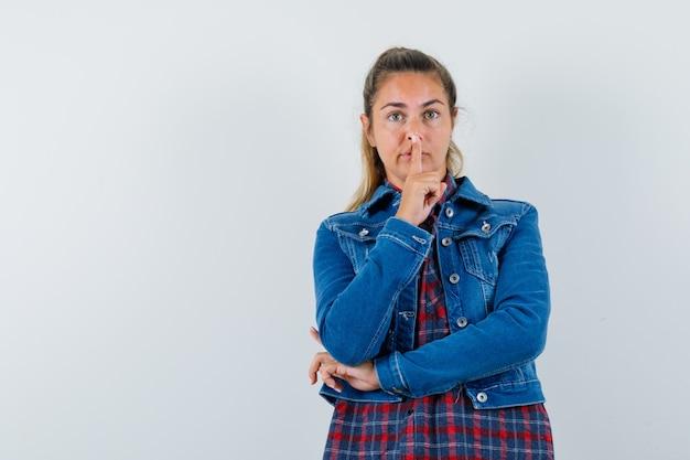 シャツを着た若い女性、沈黙のジェスチャーを示し、物思いにふける、正面図を示すジャケット。