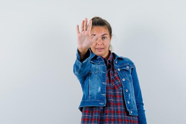 シャツを着た若い女性、停止ジェスチャーを示し、自信を持って見えるジャケット、正面図。