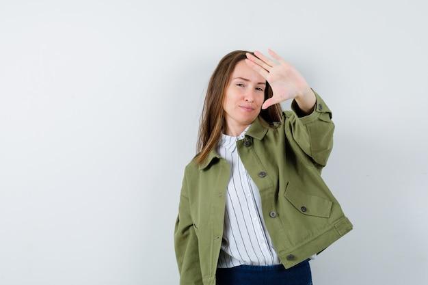 Молодая женщина в рубашке, куртке показывает жест стоп и выглядит уверенно, вид спереди.