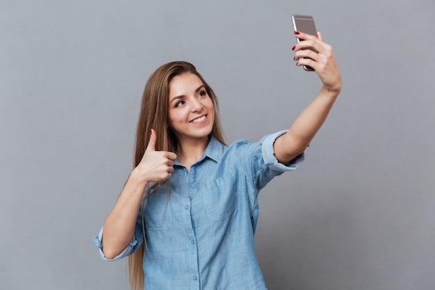 スマートフォンでselfieを作るシャツの若い女性