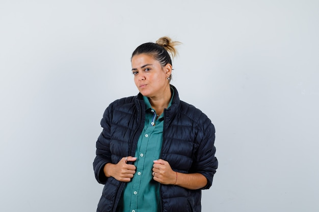 Молодая женщина в рубашке, пуховике позирует, стоя и уверенно глядя, вид спереди.