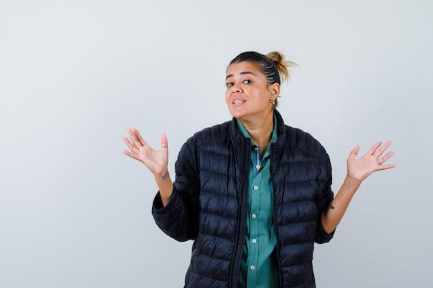 シャツを着た若い女性、手のひらを広げ、秘密を聞き、好奇心旺盛に見えるフグジャケット、正面図。