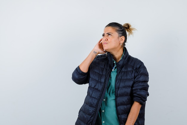 シャツを着た若い女性、耳の近くに手が付いたフグジャケット、見上げて混乱している、正面図。