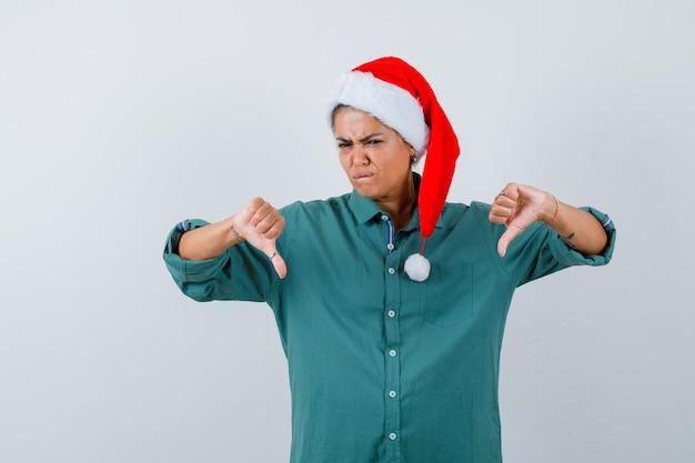 셔츠를 입은 젊은 여성, 산타 모자를 두 번 엄지손가락을 아래로 내리고 입술을 깨물고 우울해 보이는 전면 전망.