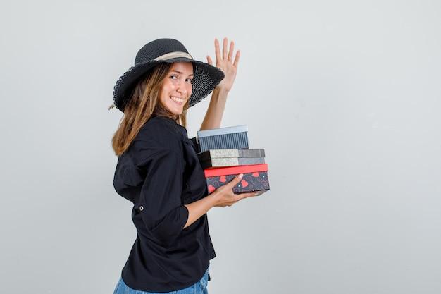 Молодая женщина в рубашке, шортах, шляпе держит подарочные коробки, поднимая руку и выглядит веселой.