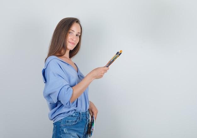Молодая женщина в рубашке, шортах держит инструменты для рисования и выглядит сладко.