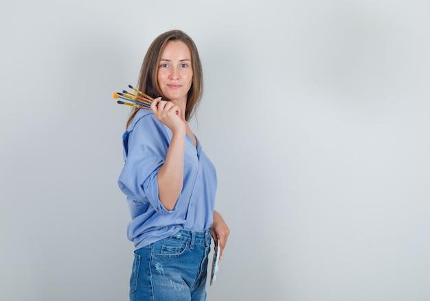 Молодая женщина в рубашке, шортах с инструментами для рисования