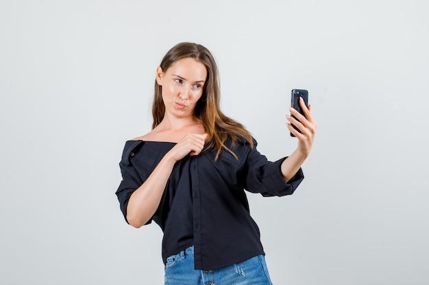 シャツを着た若い女性、スマートフォンで自分撮りをしながらポーズをとって、かわいく見えるショーツ