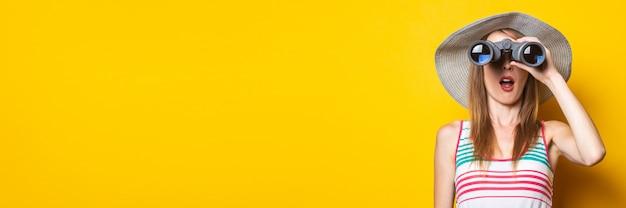 Молодая женщина в шоке от удивления в шляпе и полосатом платье удивленно смотрит в бинокль на желтом пространстве. баннер