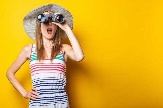 Молодая женщина в шоке от удивления в шляпе и полосатом платье удивленно смотрит в бинокль на желтом пространстве
