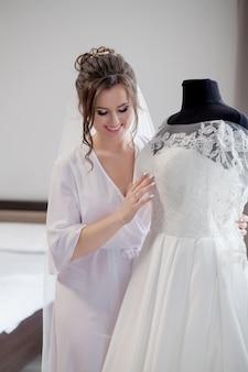 실크 가운 그녀의 웨딩 드레스를 감동과 창문 가까이 서있는 동안 웃 고있는 젊은 여자. 결혼식 날. 아름다움, 패션. 가장 행복한 신부의 날. 매 순간을 즐기십시오.