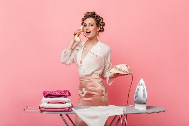 Молодая женщина в шелковой блузке разговаривает по телефону и позирует во время глажки одежды