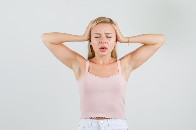 一重項、頭に手をつないで疲れているように見えるミニスカートの若い女性