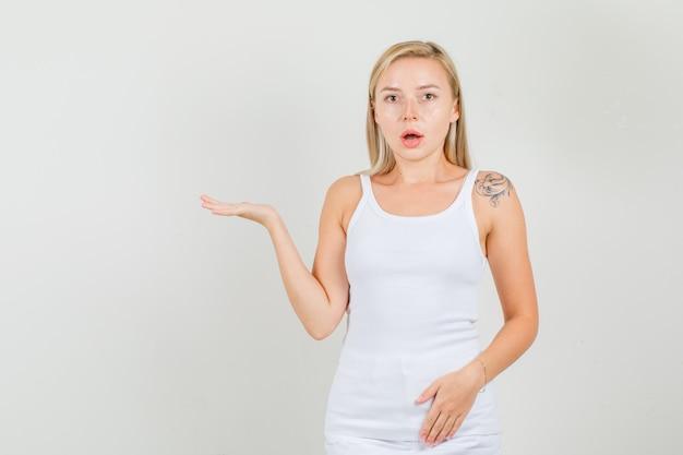 Молодая женщина в майке, мини-юбке держит открытую ладонь поднятой и выглядит удивленно