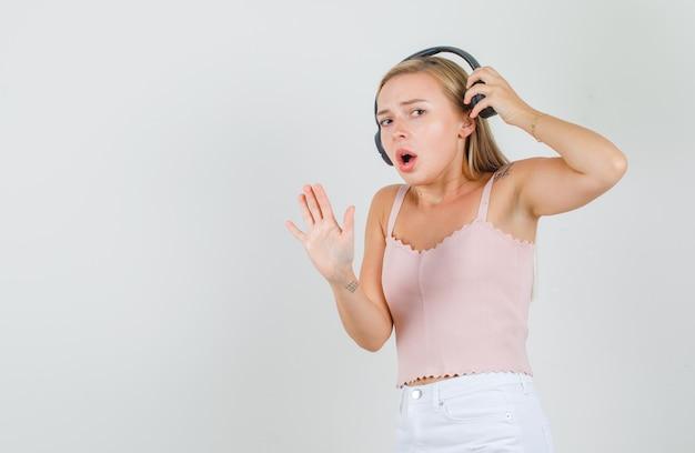 一重項の若い女性、停止ジェスチャーでヘッドフォンを脱いで心配そうに見えるミニスカート