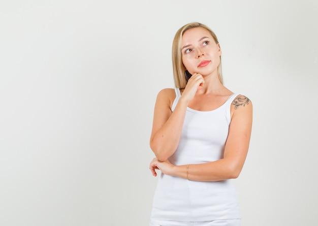 一重項の若い女性、拳で顎を支えながら考えるミニスカート
