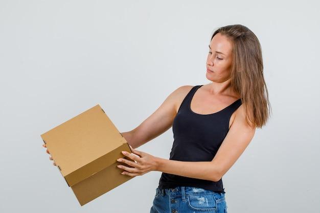 一重項の若い女性、段ボール箱を保持し、注意深く見てショートパンツ