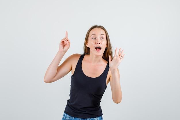 Молодая женщина в майке, шортах, указывая пальцем вверх со знаком рукой