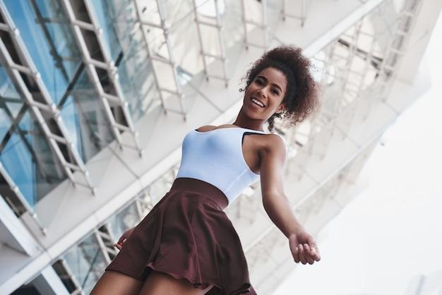 Dを探して回転している通りでスカートフリースタイルの若い女性