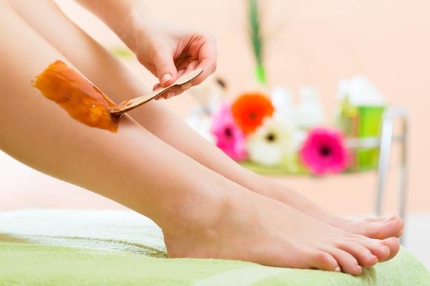 Молодая женщина в спа-салоне натирает ноги воском для удаления волос