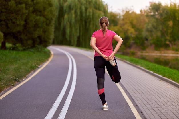 야외 공원 피트니스 훈련에서 스트레칭을 하는 등 스포츠 의류를 입은 젊은 여성